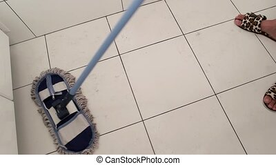 Mop sweeping tile. Dirty white floor. Cleaning product...