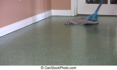 Mopping Green Floor - A housewife mops a green floor at her...