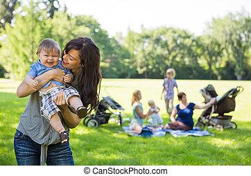 mor, bärande, glad, baby pojke, hos, parkera