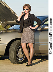 More Car Trouble - A woman on a cell phone next to a car ...