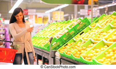 More oranges - Mother and daughter choosing ripe oranges and...