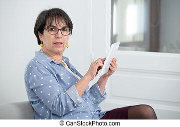 morena, digital, sentando, mulher, maduras, sofá, tabuleta, usando