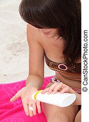 morena, em, praia, aplicando suncream