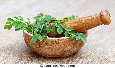 Moringa leaves and mortar pestle - Moringa leaves with...