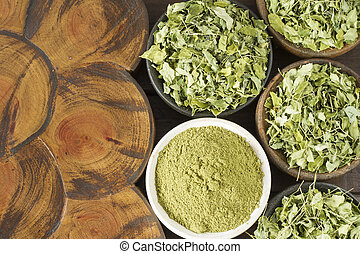 Moringa leaves and powder on the table, top view