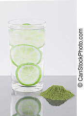 Moringa powder with lemon and glass with water isolated on white background