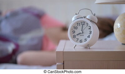 alarm clock calls 8 am, a woman wakes up and gets out of bed