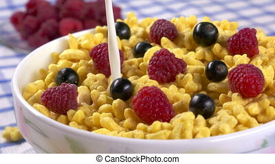 Morning breakfast pouring milk into bowl of honey stars cereal with berries