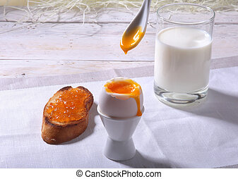 Morning Breakfast set with egg, orange jam on bread toast and milk in glass.