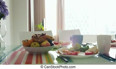 Morning breakfast table with bouquet of flower and plate...