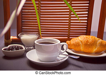 Morning breakfast with cup of hot coffee and croissant, jam on a wooden table