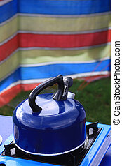 Morning Brew - A blue camping kettle on a gas stove with a...