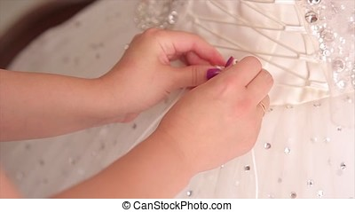 Morning bride. maid of honor helping the bride with her dress. the bride's lace up dress. Bridesmaid tying bow on wedding dress. Woman's hands lace up silk ribbon on bride's corset. Helping to lace up bride's wedding dress. Woman laces up corset on bride's delicate waist. Close-up of woman's fingers lacing up bride's corset on her back. Tender hands of young women button up lace dress on bride's back.