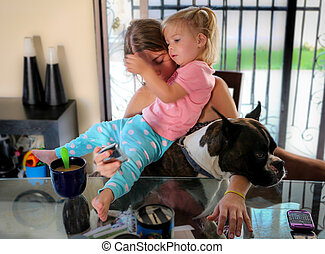 Monday morning Chaos: holding a child and a dog while trying to answer the phone and serve breakfast