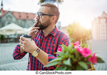 Man sitting in cafe garden and smoking cigarette in morning sunlight