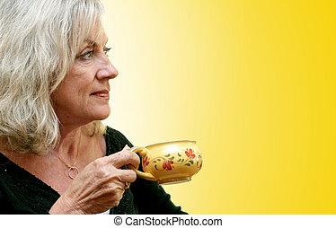 Morning Coffee - A beautiful mature woman enjoying a cup of...