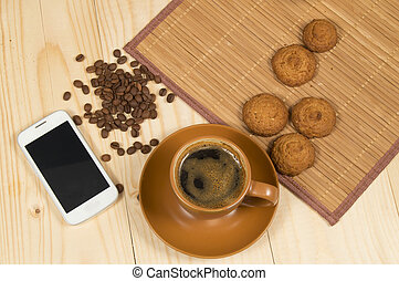 Morning coffee and biscuits on wooden Desk with mobile phone