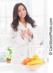 Morning coffee. Beautiful young smiling woman in bathrobe holding cup of coffee and smiling on camera