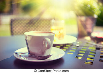 Morning coffee on the terrace. Cup of espresso on the table in sun light, garden view