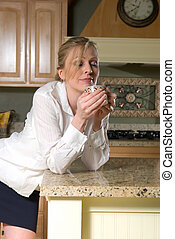 Stock photo of a woman wearing a work clothes standing in kitchen drinking a cup of coffee with eyes closed
