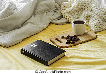 Morning Coffee With Bible Illuminated By Sunlight. Cup of coffee with Christian Bible. White bedroom. Chocolate and coffee cup.