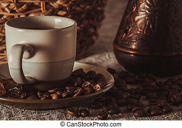 cup of coffee with beans, dark candy sugar, pot and basket