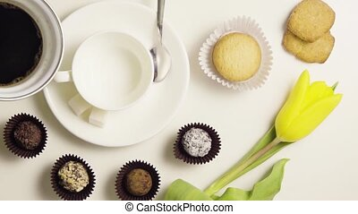 Morning cup of coffee with sweets and flowers, top view
