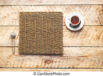 Morning cup of tea on a wooden table on straw napkin with...