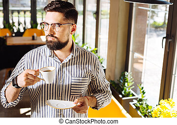 Serious young man holding a cup with coffee
