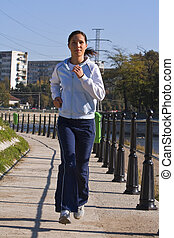 Young woman jogging in the morning on the riverside in a city. Shot with Canon 70-200mm f/2.8L IS USM