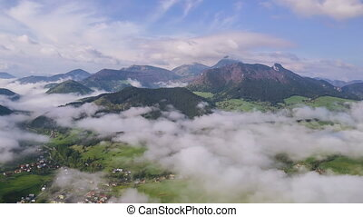 Morning flight above mist clouds in small village. Aerial slow motion time lapse hyperlapse