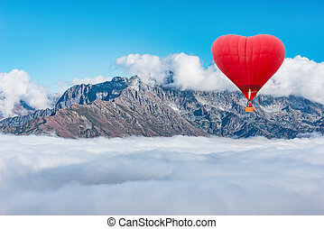 Morning flight of the hot air balloon above the mountains and clouds.