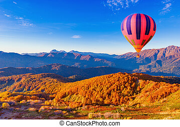 Morning flight of the hot air balloon above the mountains.