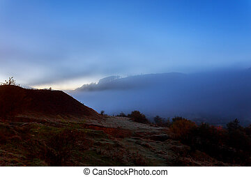 morning fog on a hillside meadow near mountain village at night in moon light