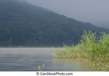 Morning fog over the mirrored mountain river against the background of mountains and blue sky