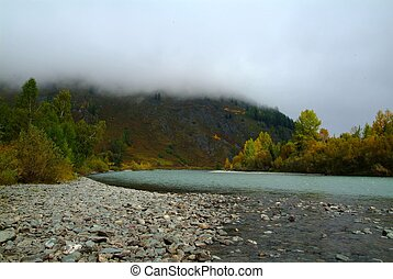 Morning fog over the Turquoise Katun with blue sky and...