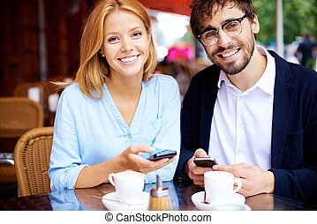 Morning in cafe - Cheerful man and woman with cellphones...