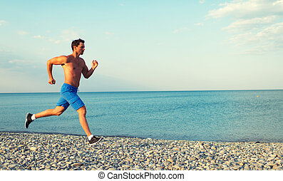 morning jog on the beach - man athlete running by the sea at...