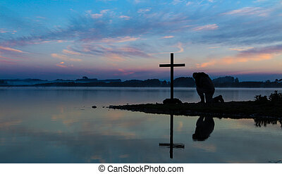 Man kneeling in pray before a cross, with a morning mist over a lake in the background.