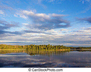 clouds over a forest lake