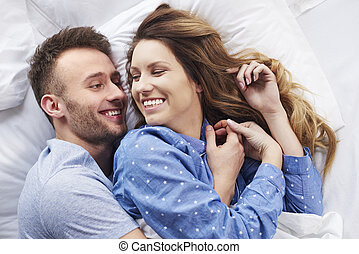 Morning laughs in bed with partner