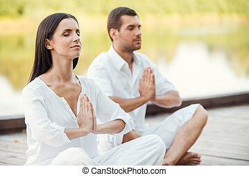 Morning meditation. Beautiful young couple in white clothing meditating outdoors together and keeping eyes closed