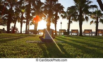 Morning meditation in the park, woman practices yoga on the...