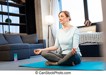 Tranquil good-looking woman meditating with closed eyes