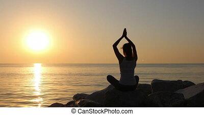 Morning meditation, woman practices yoga on the seashore,...