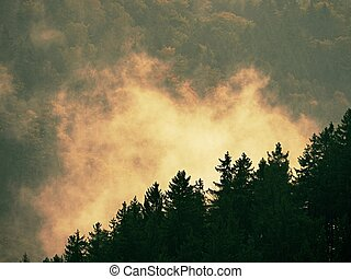 Morning mist and fog covering landscape below mountain peaks