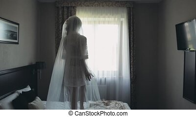Morning of beautiful bride. Young woman in white lingerie, peignoir and veil dancing on the bed before wedding ceremony.