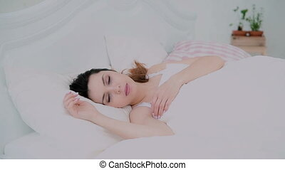 Morning of beautiful girl in light apartments. Young woman lying in bed, waking up and smile. Female looking at camera.