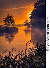 Morning on a river meander in a natural landscape with lot of fog and steam at sunrise