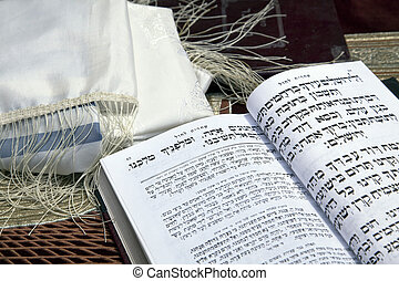 A Jewish praying shawil and a Jewish prayer book opened on one of the pages of the morning prayer, resting on a velvet tablecloth with an image of the Jewish temple from 2000 years ago. Shot in the western wall in the old city of Jerusalem.